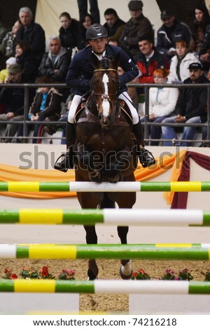 KAPOSVAR, HUNGARY - MARCH 27: Csaba Majlath jumps with his horse (Urbino) on the Masters Tournament International Jumping Competition, March 27, 2011 in Kaposvar, Hungary - stock photo