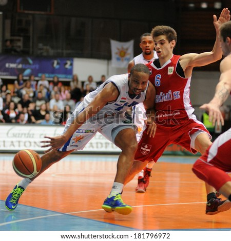 KAPOSVAR, HUNGARY - MARCH 8: Louis Hinnant (white 4) in action at a Hungarian Championship basketball game with Kaposvar (white) vs. Paks (red) on March 8, 2014 in Kaposvar, Hungary. - stock photo