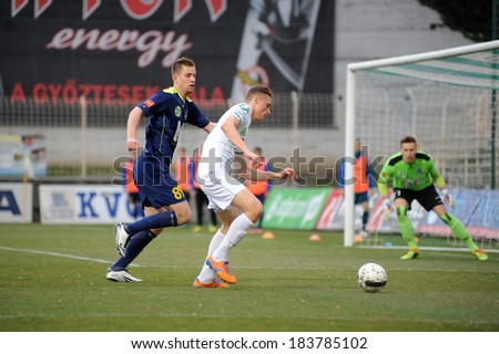 KAPOSVAR, HUNGARY - MARCH 16: Unidentified players in action at a Hungarian Championship soccer game - Kaposvar (white) vs Puskas Akademia (blue) on March 16, 2014 in Kaposvar, Hungary. - stock photo