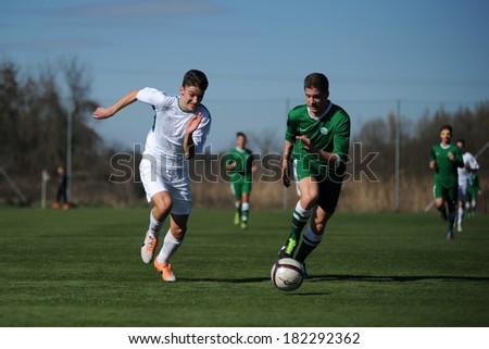 KAPOSVAR, HUNGARY - MARCH 1: Unidentified players in action at the Hungarian National Championship U17 game between Kaposvar (white) vs Ferencvaros (green) March 1, 2014 in Kaposvar, Hungary. - stock photo