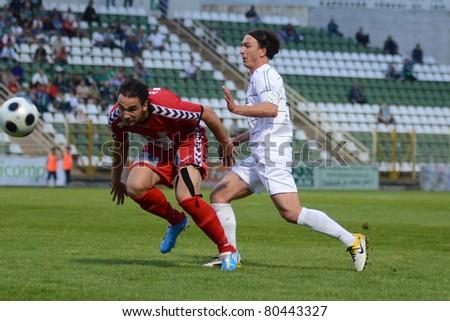 KAPOSVAR, HUNGARY - MAY 14: Lorant Olah (in white) in action at a Hungarian National Championship soccer game - Kaposvar vs Szolnok on May 14, 2011 in Kaposvar, Hungary. - stock photo