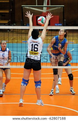 KAPOSVAR, HUNGARY - OCTOBER 10: Zsofia Harmath (R) strikes the ball at the Hungarian NB I. League woman volleyball game Kaposvar vs Veszprem, October 10, 2010 in Kaposvar, Hungary.