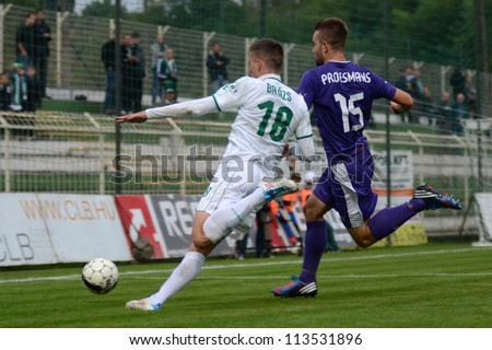 KAPOSVAR, HUNGARY - SEPTEMBER 14: Benjamin Balazs (in white) in action at a Hungarian Championship soccer game - Kaposvar (white) vs Ujpest (purple) on September 14, 2012 in Kaposvar, Hungary. - stock photo