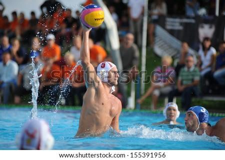KAPOSVAR, HUNGARY - SEPTEMBER 15: Jozsef Berta (5) in action at a Hungarian championship water-polo game between Kaposvar (white) and Honved (blue) on September 15, 2013 in Kaposvar, Hungary - stock photo