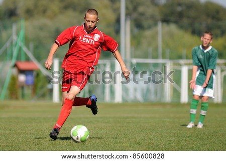 KAPOSVAR, HUNGARY - SEPTEMBER 11: Norman Szili (red) in action at the Hungarian National Championship under 15 game between Kaposvar (green)  and Lenti (red) September 11, 2011 in Kaposvar, Hungary. - stock photo