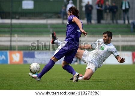KAPOSVAR, HUNGARY - SEPTEMBER 14: Pedro Sass (in white) in action at a Hungarian National Championship soccer game - Kaposvar (white) vs Ujpest (purple) on September 14, 2012 in Kaposvar, Hungary. - stock photo