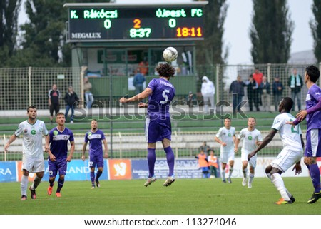 KAPOSVAR, HUNGARY - SEPTEMBER 14: Unidentified players in action at a Hungarian National Championship soccer game - Kaposvar (white) vs Ujpest (purple) on September 14, 2012 in Kaposvar, Hungary. - stock photo