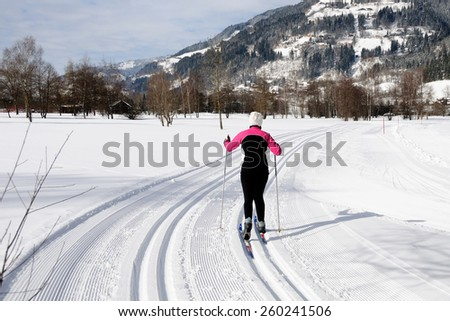KAPRUN, AUSTRIA - FEBRUARY 2, 2015. A lady run on skies in cross-country skiing area near Kaprun, Austria.   - stock photo