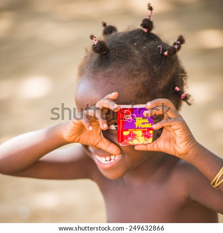 KARA, TOGO - MAR 9, 2013: Unidentified Togolese cute little girl with pigtails with Tutti Frutti candies imitates photo camera.Children in Togo suffer of poverty due to the unstable econimic situation - stock photo