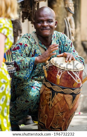 KARA, TOGO - MAR 11, 2012:  Unidentified Togolese man hits the drum for the religious voodoo dance. Voodoo is the West African religion - stock photo