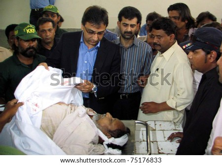 KARACHI, PAKISTAN - APR 12: Sindh Information Technology Minister, Raza Haroon, looks dead body of a government employee who was killed in firing incident on April 12, 2011 in Karachi. - stock photo