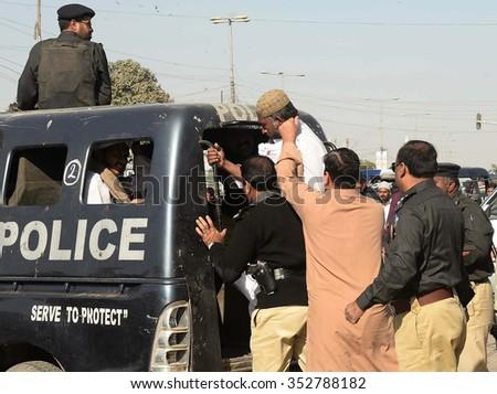 KARACHI, PAKISTAN - DEC 18: Police detained protestors moving ahead towards Red Zone during demonstration in favor of Mumtaz Qadri murderer of former Governor Punjab on December 18, 2015 in Karachi. - stock photo
