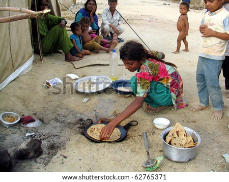KARACHI, PAKISTAN - OCT 10: Flood affected girl prepares food for her family with the help of woods at flood affectees relief camp on October 10, 2010 in Karachi, Pakistan.