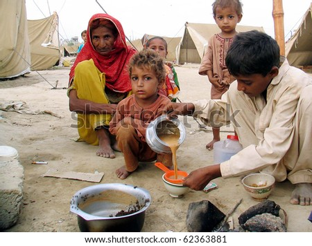 KARACHI, PAKISTAN, OCT 03: Flood affectee child serves tea to his family members at their make-shift tent house at relief camp established at Hawks Bay area on October 3, 2010 in Karachi, Pakistan.