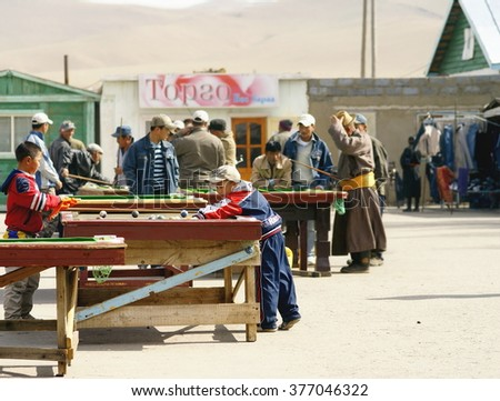 KARAKORUM , MONGOLIA - 30-04-2008; Men of the little town Karakorum are gathered on a  square in the centre of the town, to play billiards at outdoor billiard tables