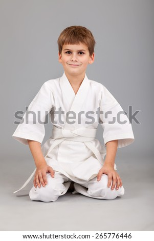 Karate boy in white kimono is sitting isolated on gray background - stock photo
