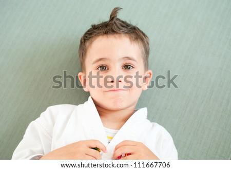 Karate boy relaxing in sport hall lying on the floor pad - stock photo