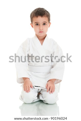 Karate boy sitting in white kimono isolated on white - stock photo