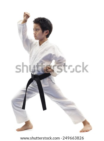 Karate kid wearing white gi and black belt performing rising block in front stance.