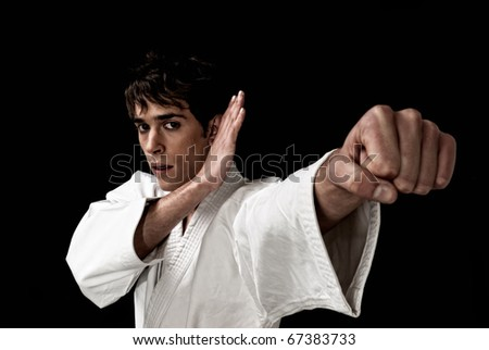 Karate male fighter young close-up high contrast on black background. - stock photo