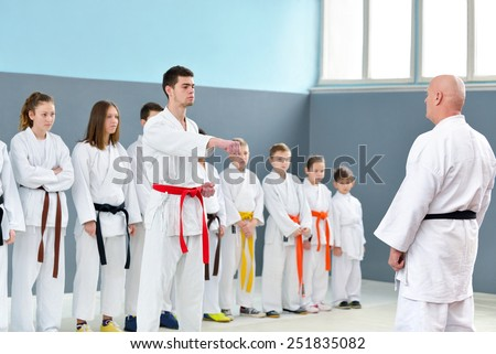 Karate master shows a group of young martial arts - stock photo