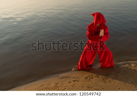 Karate monk wearing red hood meditating at the lake shore