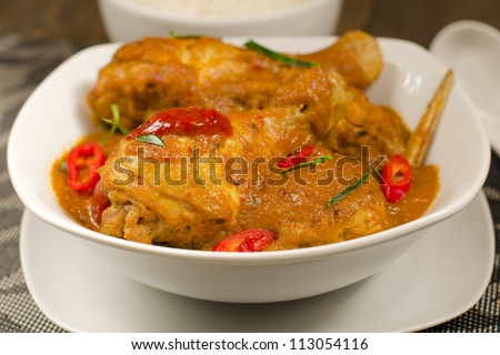 Kari Kapitan - Malaysian spicy chicken curry with coconut milk garnished with kaffir lime leaves, red chilies and sambal oelek. Served with rice. Close up. Traditional Nyonya Cuisine. - stock photo