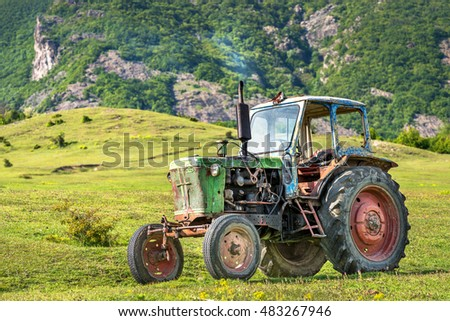 Karlovo, Bulgaria - May 2, 2016: Green color russian vintage garden tractor T25 is parked in country house yard.