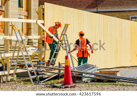 Karlskrona, Sweden - May 3, 2016: Two male carpenters constructing a wooden fence at a site outside a church in the town square. They carry a plank.