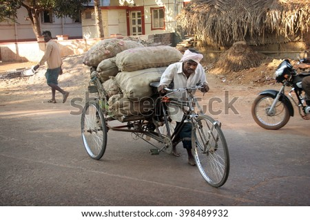 Karnataka, India - February 05, 2006: Cycle rickshaw with cargo load in the streets in Hospet, India. Cycle rickshaws were introduced in the 1940's and have a fixed quota of licenses.