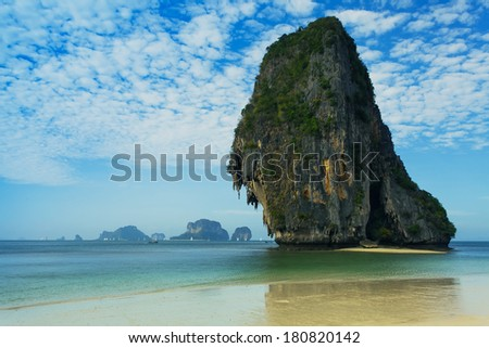karst mountains and Traditional Boat on Tropical green beach, background blue sky with clouds. Andaman Sea, Krabi, Railay, Thailand