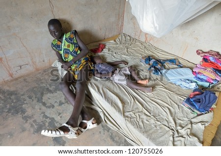 KARTIAK, SENEGAL-SEPT 18: unidentified African teenager sits in his room on Sept. 18,2012 in Kartiak,Senegal.The region of Casamance,south of Senegal,is a very poor area according Internat. statistics
