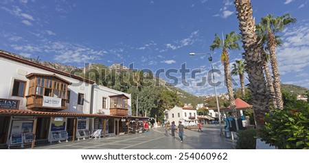 KAS, TURKEY - OCTOBER 15, 2009: Town Square named Cumhuriyet Meydani with walking men and traditional town houses in the Village Kas in Turkey. Kas is a small fishing, yachting and tourist town. - stock photo