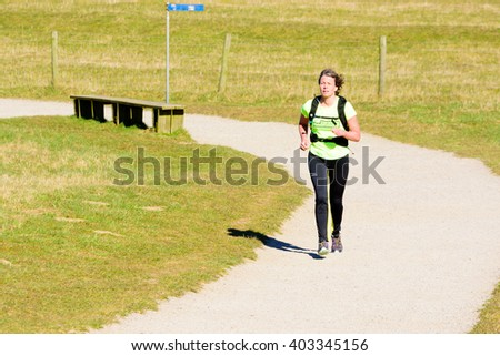 Kaseberga, Sweden - April 1, 2016: Female jogger running at gravel path surrounded by grass. Real people in everyday life in public area.