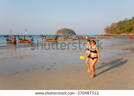 KATA BEACH, THAILAND - CIRCA FEBRUARY, 2015:  People in the early morning on the beach of Kata. This is one of the most popular beaches among tourists in Phuket. - stock photo