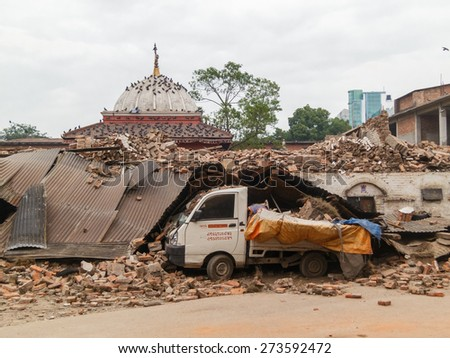 KATHMANDU, NEPAL - APRIL 26, 2015: Crashed van by a collapsed building after the 7.8 earthquake hit Nepal on 25 April 2015. - stock photo