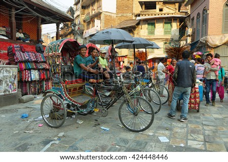 KATHMANDU, NEPAL - APRIL 9 2016: men in their rickshaws waiting for clients in the heart of the old town in Kathmandu, Nepal