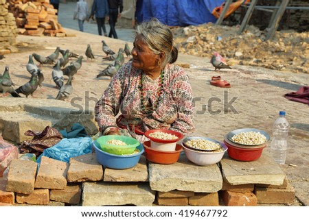KATHMANDU, NEPAL - APRIL 9 2016: old woman selling corn in front of Durbar Square of Kathmandu in Nepal.