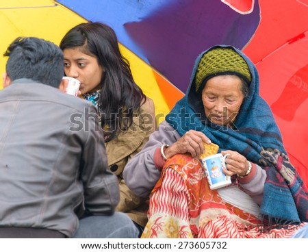 KATHMANDU, NEPAL - APRIL 26, 2015: People drinking tea on an open ground at Chuchepati after their first night outside after the 7.8 earthquake on 25 April 2015. - stock photo