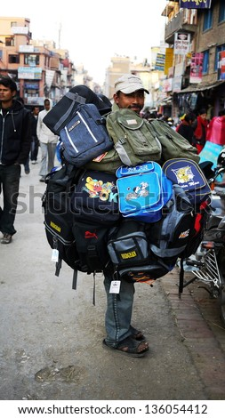 KATHMANDU, NEPAL - JANUARY 29: a hawker sells his bags, surrounding by bags in Katmandu on 29 Jan 2010. The United Nations list Nepal as one of the Least developed country in the world - stock photo
