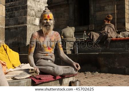 KATHMANDU, NEPAL - JANUARY 2: Sadhu (holy man) seeks alms in front of at Pashupatinath Temple on the banks of River Baghmati, January 2, 2009 in Kathmandu, Nepal. - stock photo