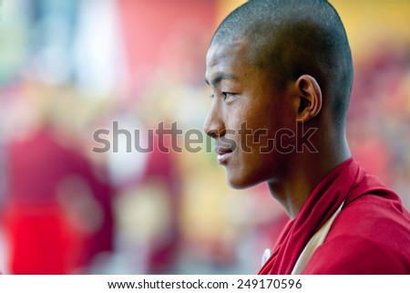 KATHMANDU, NEPAL - MARCH 25: Smiling Buddhist monk walking in a religious procession during Cham mystery at Shechen monastery on March 25, 2010 in Kathmandu, Nepal. - stock photo