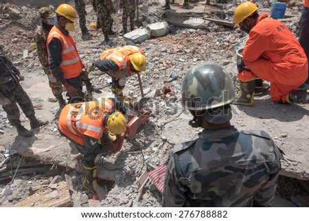 KATHMANDU, NEPAL - MAY 1, 2015: soldiers with debris of buildings near Sobhavagbati bridge damaged after the major earthquake on 25 April 2015. - stock photo