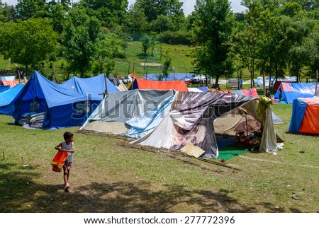 KATHMANDU, NEPAL - MAY 13, 2015: The Nepal Golf Course next to Kathmandu airport is used as a makeshift campsite after a 7.3 earthquake hit Nepal on May 12, 2015. - stock photo