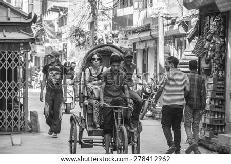 KATHMANDU, NEPAL - OCTOBER 07, 2014: Rickshaw with tourists in the back in Thamel area, Kathmandu.  - stock photo