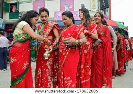 Kathmandu, Nepal - September 18, 2012: Hindu women in traditional red sari celebrating the Haritalika Teej festival on the streets of Kathmandu, Nepal - stock photo