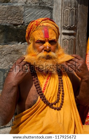 KATHMANDU, NEPAL - SEPTEMBER 21: Holy Sadhu man with traditional painted face, blessing in Pashupatinath Temple. September 21, 2012 in Nepal, Kathmandu.