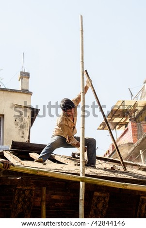 KATMANDU, NEPAL - MAR 6, 2017: Unidentified Chhetri boy repairs the roof. Chhetris is the most populous ethnic group of Nepal
