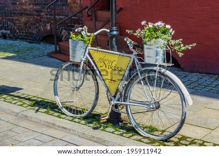 KATOWICE, POLAND - MAY 31, 2014: Bike as a signpost and advertisement of Nikisz Art Gallery in Nikiszowiec, district of Katowice. The place is historic coal miners settlement built between 1908-1918. - stock photo