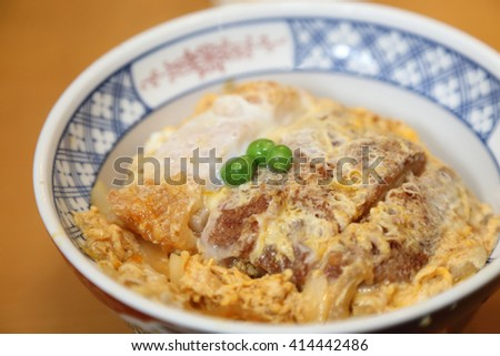 ... deep fried pork cutlet topped with egg on steamed rice in a bowl